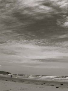 black and white photo of a person walking on an ocean beach in the distance
