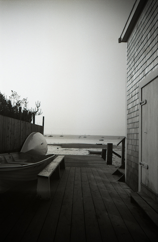b/w scene of dock, canoe and sea in provincetown, ma