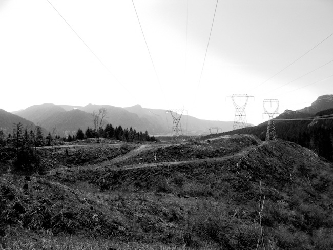 black and white photo of high tension cables and landscape